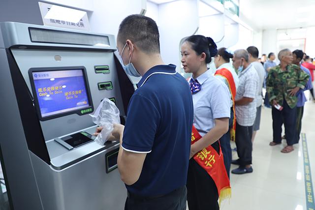 邮储银行贵港市分行工作人员在引导客户使用纸硬币兑换机.JPG